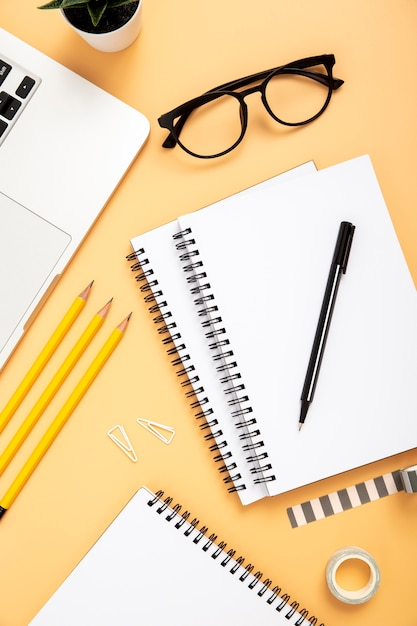 Organised arrangement of desk elements on orange background Free Photo