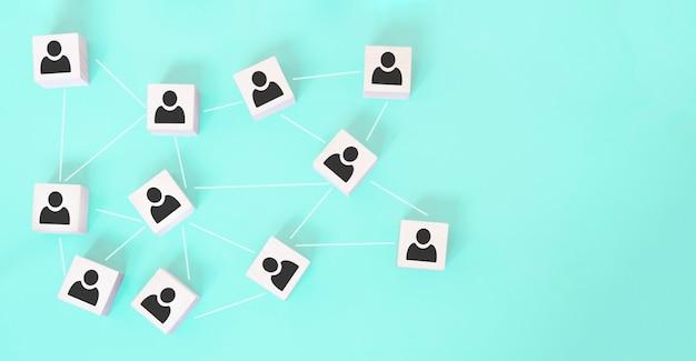 Организационная структура, создание команды, управление бизнесом или концепции человеческих ресурсов. иконы человека на деревянных кубиках связаны друг с другом. Premium Фотографии