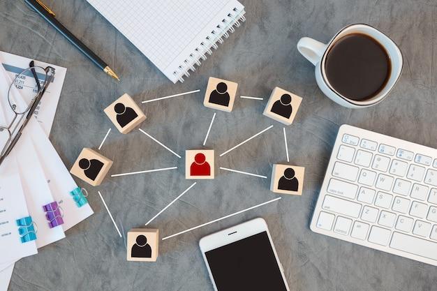 조직 구조, 팀 빌딩, 채용, 관리 및 인적 자원 개념. 서로 연결된 나무 큐브에 사람 아이콘. 프리미엄 사진