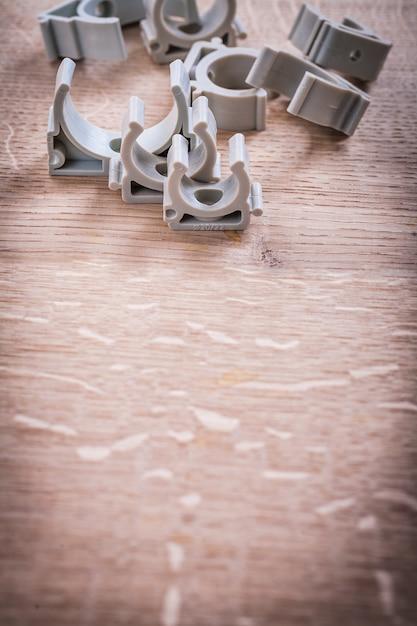 木の板に組織されたcopyspaceプラスチックパイプ固定具 Premium写真
