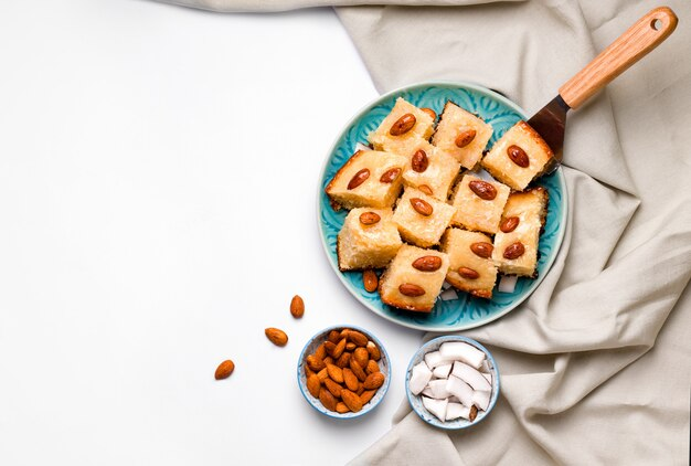 Oriental cuisine sweet arabic busbus semolina pie on a blue plate on a white background Premium Phot