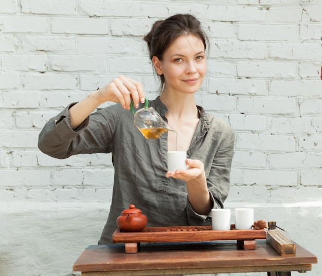 Oriental master of tea ceremony with white brick wall on the background. Premium Photo