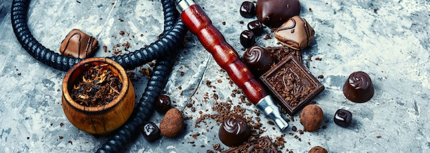 Oriental smoking hookah with a taste of chocolates. chocolate tobacco flavor.summer party Premium Photo