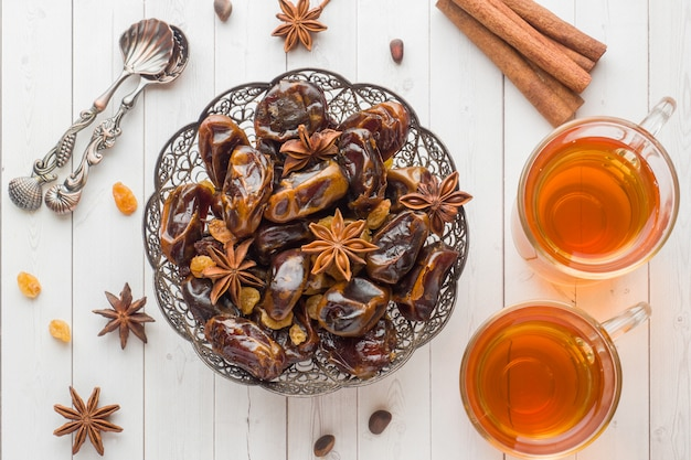 Oriental sweets, dried fruit dates and raisins, cinnamon and star anise in a plate. Premium Photo