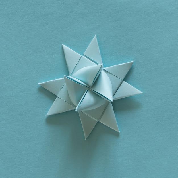 Оригами 3d звезды, голубые, на голубом фоне. концепция украшения. орнамент. современное бумажное искусство и ремесло. Бесплатные Фотографии
