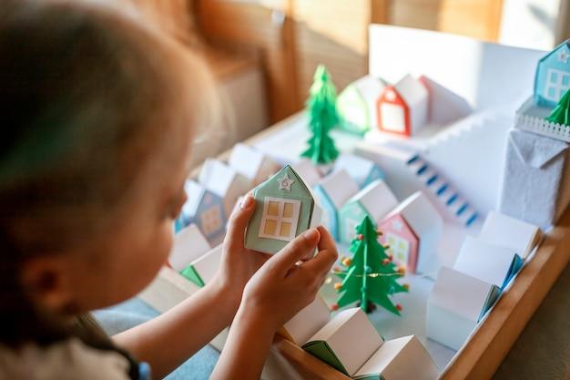 折り紙アドベントカレンダー。小さな紙の家を見ているかわいい女の子、子供たちとの季節の活動 Premium写真