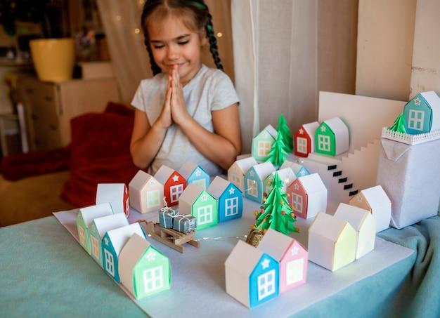 折り紙アドベントカレンダー。数の小さな紙の家を見ているかわいい女の子 Premium写真