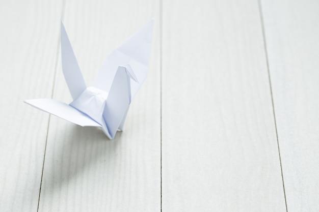 Оригами бумажная птица на белом столе Premium Фотографии