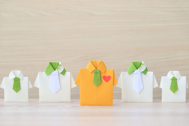 Origami yellow shirt with tie leading among small yellow shirt on wooder background Premium Photo