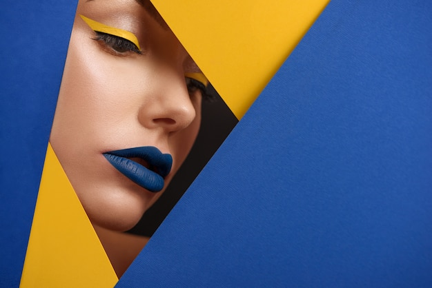 Original beaty close up of girl's face surronded by blue and yellow carton. Premium Photo