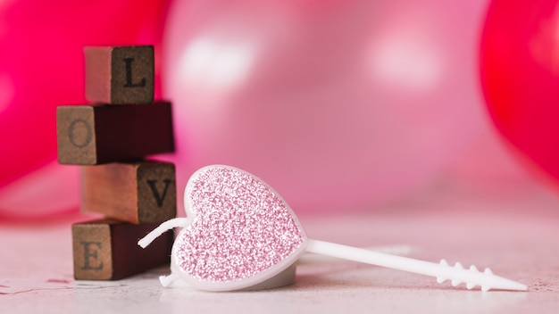 Ornament candle in form of heart near love inscription of wood wands Free Photo