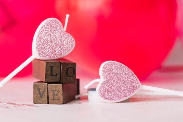 Ornament candles of symbol of heart near love title of wooden wands Free Photo