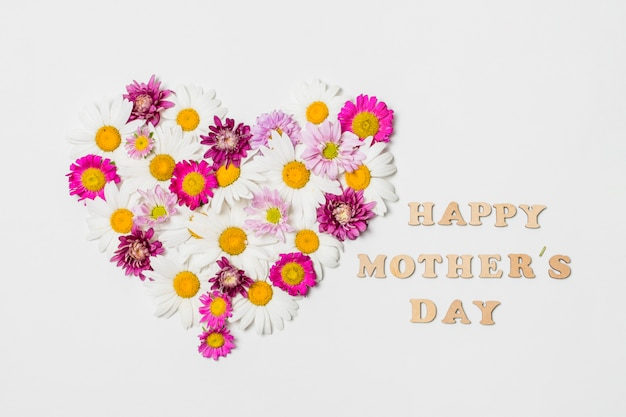 Ornamental heart of bright flowers near happy mothers day title Free Photo