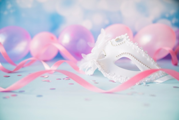 Ornamental white mask in pink streamers Free Photo