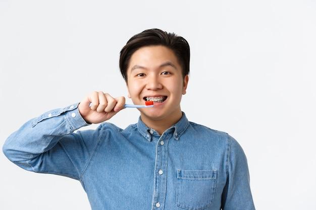 歯列矯正、歯科治療、衛生概念。ブレースで歯を磨く、歯ブラシを保持する、白い壁に立っているフレンドリーな笑顔のアジア人のクローズアップ 無料写真