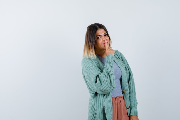 Ortrait of female showing silence gesture in casual clothes and looking sensible front view Free Photo