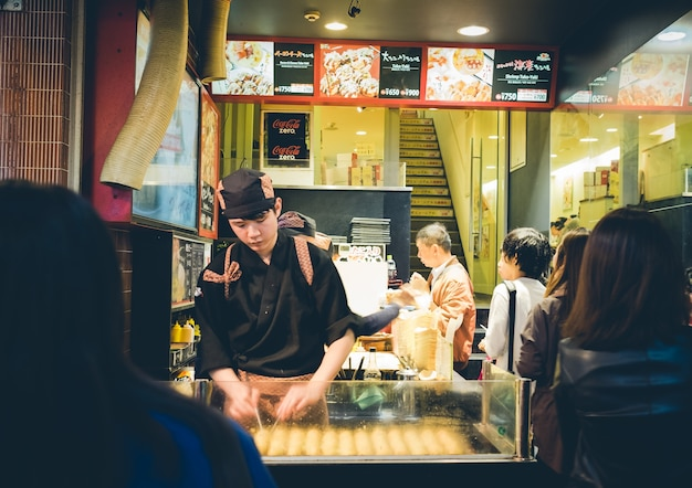 Osaka、japan  -  9月、1:身元不明のシェフは、たこ焼きを準備します 無料写真