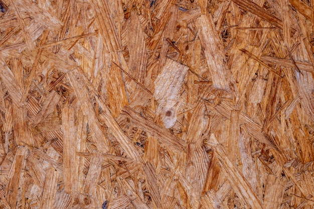 Osb boards are made of brown wood chips sanded into a wooden background. Premium Photo