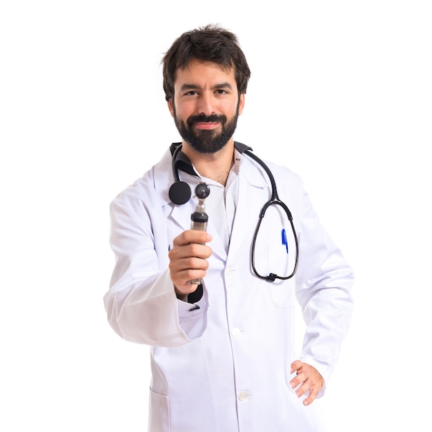 Otorhinolaryngologist with his otoscope over white background Free Photo