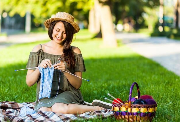 公園でoudoorsを編む若い女性 Premium写真