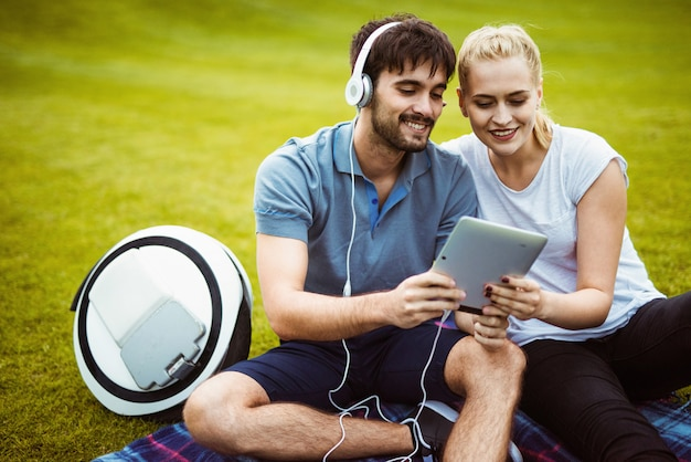 Сouple sitting on the grass and having fun with a tablet Premium Photo