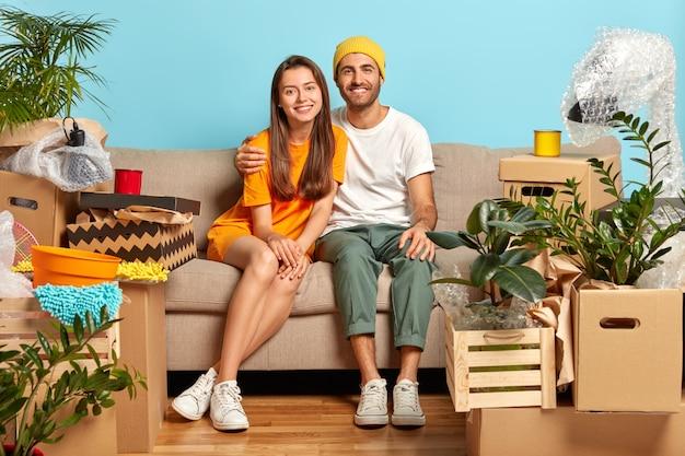 우리의 첫 번째 집. 신혼 부부는 새 아파트에 소지품과 함께 상자를 가져옵니다 무료 사진