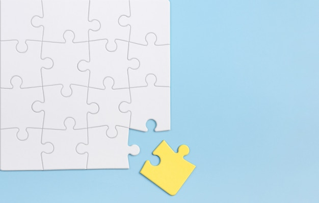 Out of the box thinking and individuality concept. yellow puzzle against white ones on blue wall. Premium Photo