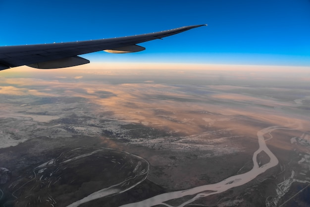 Out side above view from airplane side windows when sunrise, transportation and traveler concept Premium Photo