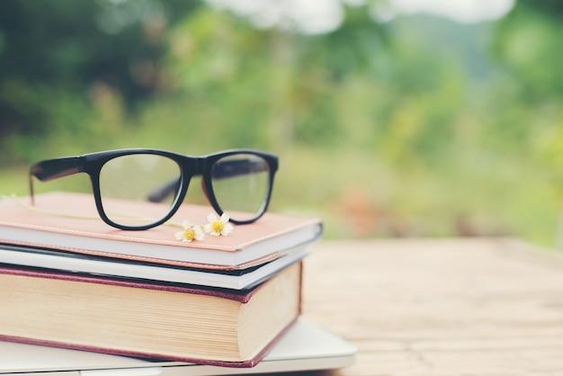 帳と眼鏡の読み取り用とぼやけ自然outdの上に書きます 無料写真