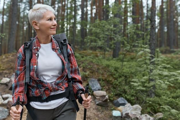 Outdor портрет счастливой европейской пенсионерки с рюкзаком и шестами, наслаждающейся красивой природой во время скандинавской ходьбы в сосновом лесу. Бесплатные Фотографии