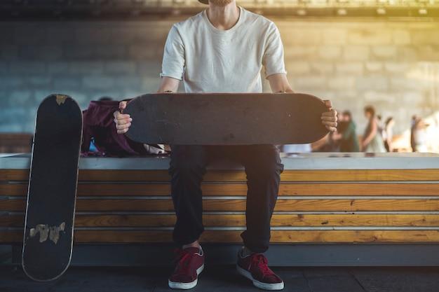 スケートボードoutdoo.rsとベンチに座っている若いヒップスターの都市通りの肖像画 Premium写真