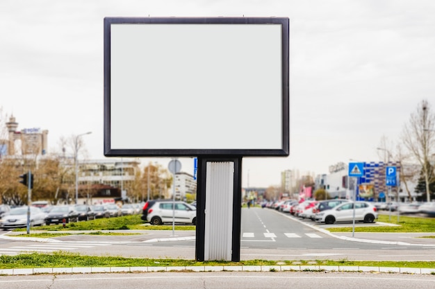 An outdoor advertising billboard in front of parking lot Free Photo