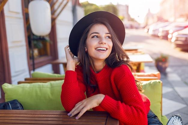Внешний портрет моды осени грациозно усмехаясь молодой женщины в уютном теплом связанном пуловере. милая леди, сидя в кафе, пить кофе Бесплатные Фотографии