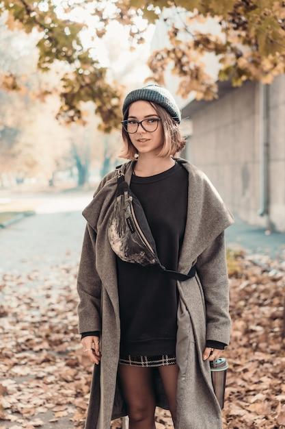 유럽 도시의 거리에서 걷는 젊은 여자의 야외 가을 초상화. 무료 사진