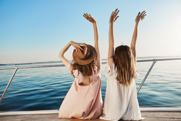 Outdoor back view of two young female on luxury vacation, waving at seaside while sitting on yacht. Free Photo