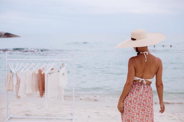 Открытый пляжный магазин вязаной одежды выбор женщины, что купить на напольной вешалке концепция летнего трикотажа Бесплатные Фотографии