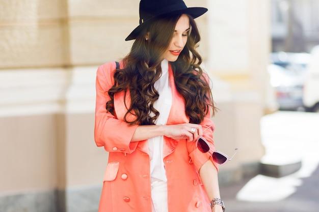 屋外は黒い帽子、ピンクのスーツ、古い通りでポーズをとって白いブラウスでセクシーなスタイリッシュなカジュアルな女性のファッションポートレートを閉じます。春、秋の晴れた日。ウェーブのかかった髪型。 無料写真