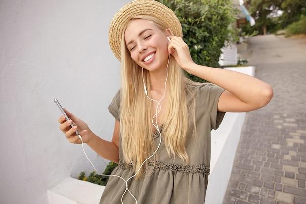 緑の通りを歩きながら、音楽トラックを楽しみながらヘッドフォンで音楽を聴いて魅力的な幸せな女性の屋外のクローズアップ 無料写真