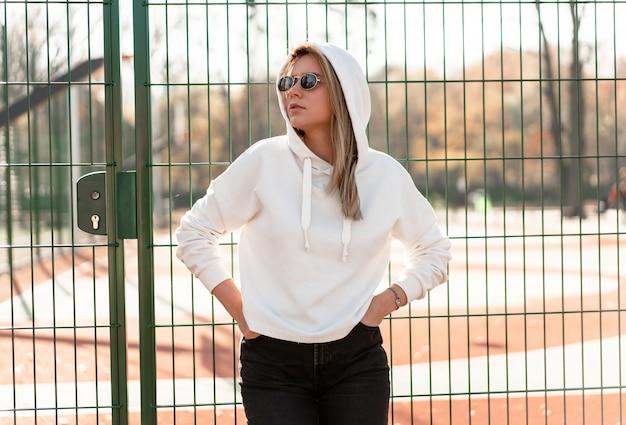 スポーツグラウンド近くの白いパーカーセーターに身を包んだサングラスで長い髪の若い美しい女性の肖像画間近で屋外。若者文化夏の娯楽 Premium写真