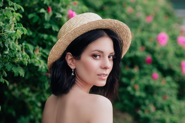 Outdoor close up portrait of young beautiful happy smiling woman wearing stylish straw hat. Premium Photo