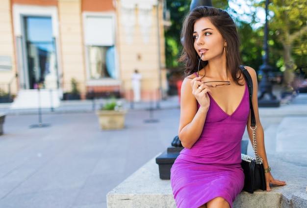 誰かを待っていると夢を見て、路上で自由な時間を楽しんでいるスタイリッシュなベルベットのドレスでかなり優雅な女性のアウトドアファッションのイメージ。暖かい日当たりの良い色。ブルネットのウェーブのかかった髪型。 無料写真