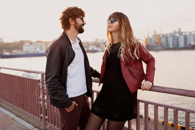 Открытый модный образ стильной пары в повседневной одежде, кожаной куртке и солнцезащитных очках, стоящих на мосту. красивый мужчина с бородой со своей девушкой проводит романтическое время вместе. Бесплатные Фотографии