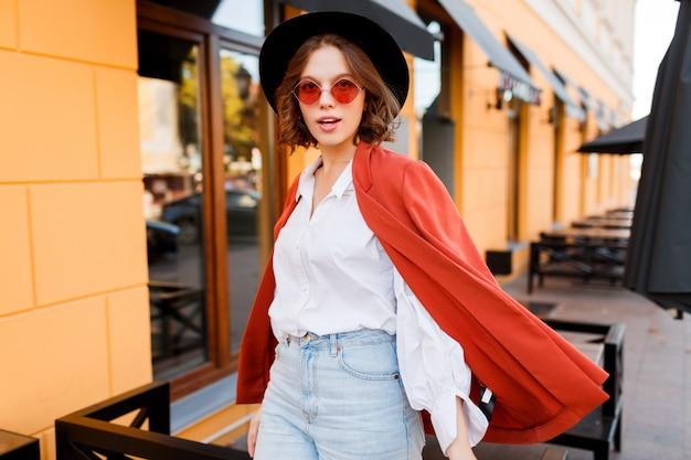 オレンジ色のジャケットと週末に日当たりの良い街を歩いて白いブラウスのエレガントな若い女性のアウトドアファッションのイメージ。 無料写真