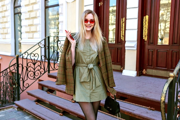 Outdoor fashion image of stunning blonde model woman posing on the paris street, trendy outfit with oversized modern jacket, autumn spring mid season, warm toned colors. Free Photo