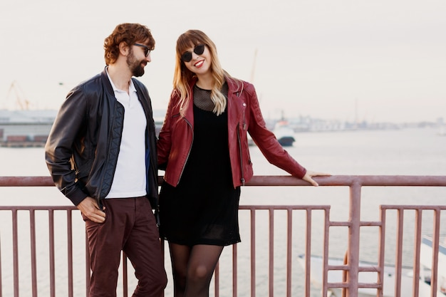 Outdoor fashion image of stylish couple in casual outfit, leather jacket and sunglasses standing on the bridge.  handsome man with beard with his girlfriend spending romantic time together. Free Photo