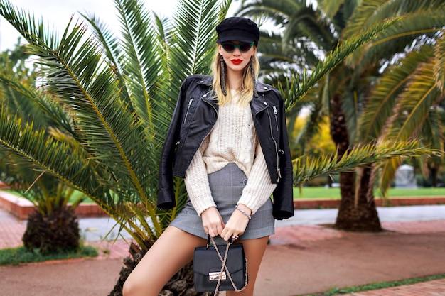 Immagine di moda all'aperto di donna elegante ed elegante in posa nelle strade di barcellona vicino a palme, con indosso giacca di pelle, berretto, occhiali da sole retrò, borsa piccola, maglione bianco accogliente e gioielli alla moda, minigonna. Foto Gratuite