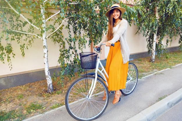 자작 나무와도 그녀의 복고풍 자전거를 타고 아름 다운 젊은 갈색 머리 여자의 야외 패션 라이프 스타일 초상화. 우아하고 세련된 옷 모자와 따뜻한 가디건을 착용하십시오. 가을 분위기. 무료 사진