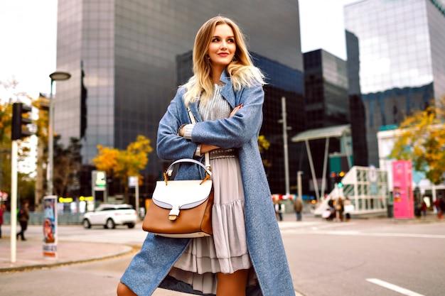 モダンな建物のエリアを歩いて、青いコートとフェミニンなグレーのドレスを着ている金髪のかなり若い実業家のアウトドアファッションライフスタイルの肖像画。 無料写真
