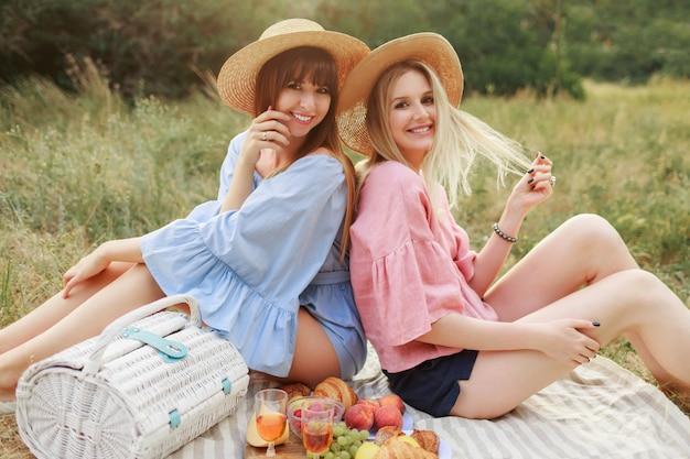 Foto di moda all'aperto di due donne attraenti in cappello di paglia e vestiti estivi che godono di piknik. Foto Gratuite