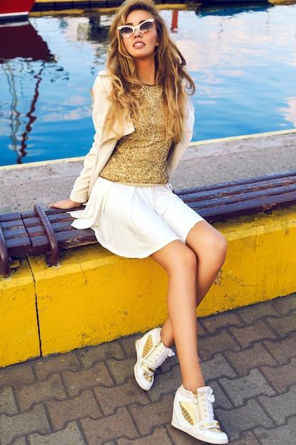Il ritratto di moda all'aperto della bellissima modella, che indossa un vestito elegante e caldo con cappotto e scarpe da ginnastica, ha i capelli biondi arricciati alla moda, seduti allo yacht club della città. stile di strada autunnale. Foto Gratuite